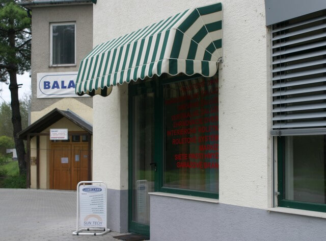 Zeleno-biela markíza pred vchodom do domu
