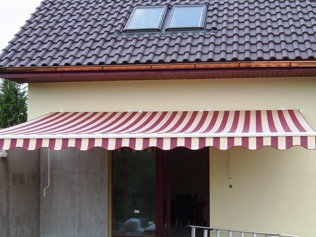 Červeno-biela markíza pred vchodom do domu